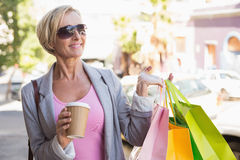 Happy mature woman walking with her shopping purchases Stock Photography