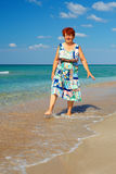 Happy mature woman walking the surf on the beach royalty free stock photos