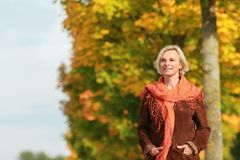 Happy mature woman walks in front of golden autumn leaves Royalty Free Stock Photo