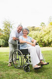 Happy mature woman in wheelchair with partner Stock Image