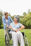 Happy mature woman in wheelchair talking with daughter Royalty Free Stock Photography