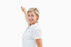 Happy mature woman writing and smiling Stock Images