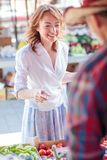 Happy mature woman buying fresh organic vegetables in a local marketplace stock photography