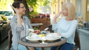 Happy women friends doing high-five and laughing in outdoor cafe in summer. Happy mature women friends are doing high-five and laughing sitting in outdoor cafe stock video