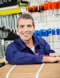 Happy Mature Worker Leaning On Tool Package Royalty Free Stock Photography