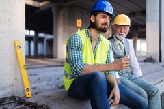 Happy mature and young engineer, architect, worker sitting at building site and resting royalty free stock images