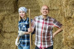 Happy mature and young farmers in hayloft Stock Photos