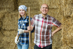 Happy mature and young farmers in hayloft Royalty Free Stock Photo