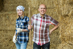 Happy mature and young farmers in hayloft Stock Photo