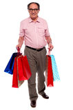 Happy matured man carrying shopping bags. Full length portrait Stock Photo