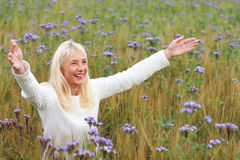 Happy matured woman with arms spread in flower field Royalty Free Stock Images