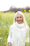 Happy matured woman in flowerfield Stock Images