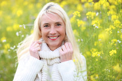 Happy matured woman in flowerfield Royalty Free Stock Photography