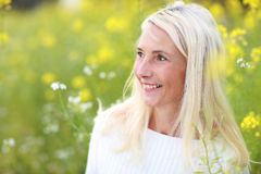Happy matured woman in flowerfield. Happy matured woman with scarf smiling in beautiful flowerfield Royalty Free Stock Image