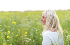 Happy matured woman in flowerfield Stock Photos