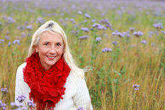 Happy matured woman in flowerfield Stock Image