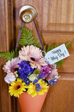 Happy May Day gift of flowers on door. Stock Photos