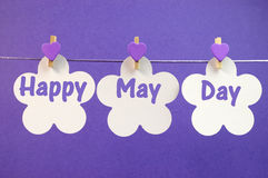 Happy May Day greeting message written across white flower cards with purple heart pegs hanging from pegs. On a line for May Day, May 1, celebration Royalty Free Stock Image