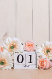 Happy May Day white block wood calendar decorated with spring flowers on wood table. Royalty Free Stock Image