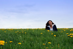Happy in the meadow. A happy young lady in a flowering field royalty free stock images