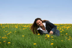 Happy in the meadow. A happy young lady in a flowering field against a blue sky stock photography