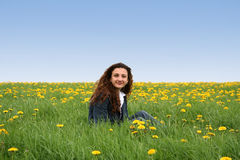 Happy in the meadow IV. A young lady in a flowering spring field royalty free stock photo