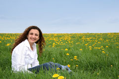 Happy in the meadow V. A happy young lady in a flowering spring field royalty free stock photography