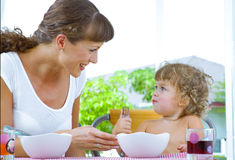 Happy meal. Portrait of young woman feeding her baby daughter Stock Image