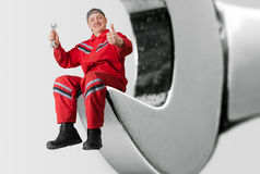 Happy mechanic in big spanner Stock Photos