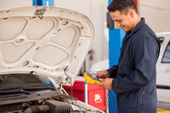 Happy mechanic checking a battery Royalty Free Stock Photography