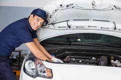 Happy Mechanic Examining Car Engine royalty free stock images