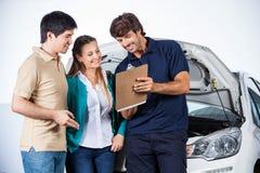 Happy Mechanic Explaining Documents To Couple Royalty Free Stock Images