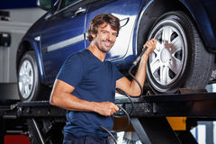 Happy Mechanic Filling Air Into Car Tire At Garage Stock Photography