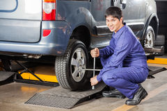 Happy Mechanic Fixing Car Tire With Rim Wrench Royalty Free Stock Photography