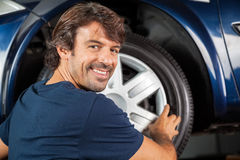 Happy Mechanic Fixing Hubcap To Tire Royalty Free Stock Photos