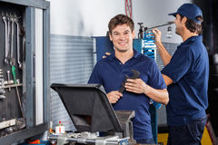 Happy Mechanic Holding Adjustable Wrench. Portrait of happy male mechanic holding adjustable wrench at garage while colleague working in background Royalty Free Stock Images