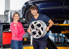 Happy Mechanic Holding Alloy With Customer At Garage. Portrait of happy mechanic holding alloy while standing with female customer at garage Royalty Free Stock Images