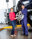 Happy Mechanic Holding Alloy With Customer At. Portrait of happy mechanic holding alloy while standing with female customer at garage Stock Photo