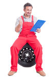 Happy mechanic holding clipboard and showing like or thumb-up ge Stock Photo
