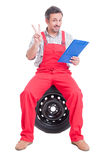 Happy mechanic holding clipboard and showing peace or victoy sig Stock Photography