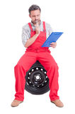 Happy mechanic holding clipboard and thinking Royalty Free Stock Photos