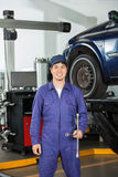 Happy Mechanic Holding Rim Wrench At Garage Royalty Free Stock Image