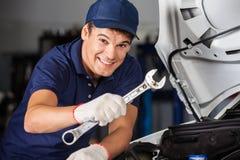 Happy Mechanic Holding Wrench While Examining Car stock photography