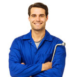 Happy Mechanic Holding Wrench. Portrait of happy male mechanic standing with arms crossed holding wrench over white background. Horizontal shot Royalty Free Stock Photo