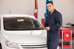 Happy mechanic inspecting a car Royalty Free Stock Photography