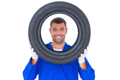 Happy mechanic looking through tire Stock Photography