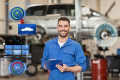 Happy mechanic man with clipboard at car workshop. Car service, repair, maintenance and people concept - happy smiling auto mechanic man or smith with clipboard Stock Images