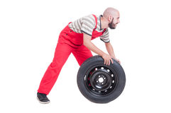 Happy mechanic pushing a  new car wheel Stock Photography