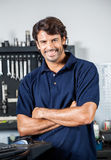 Happy Mechanic Standing Arms Crossed. Portrait of happy male mechanic standing arms crossed in auto repair shop Stock Images