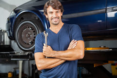 Happy Mechanic Standing Arms Crossed At Repair Shop. Portrait of happy mechanic holding wrench while standing arms crossed at repair shop royalty free stock photo